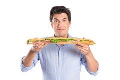 Junger Mann, der großes Sandwich hält Stockfoto