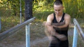 Junger Mann in der guten körperlichen Verfassung, wird auf den Stangen engagiert stock video footage