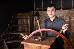 Junger Mann, der hölzernes antikes Schiff steuert Lizenzfreie Stockbilder