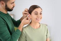 Junger Mann, der Hörgerät in das Ohr der Frau einsetzt stockfoto