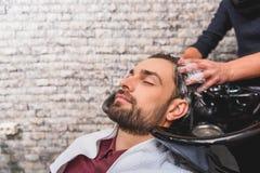 Junger Mann, der hairwash am Schönheitssalon genießt Stockfoto
