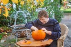 Junger Mann, der Halloween-Kürbis bildet Stockbild