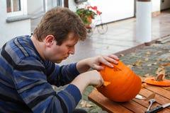 Junger Mann, der Halloween-Kürbis macht Stockbild