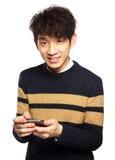 Junger Mann, der Handy auf weißem Hintergrund verwendet Lizenzfreies Stockfoto