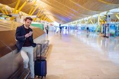 Junger Mann, der Handy am Flughafen wartet und verwendet Stockfotos