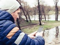 Junger Mann, der Handy im Park verwendet Stockfotografie