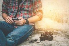 Junger Mann, der Handy mit alter Retro- Kamera verwendet Lizenzfreies Stockfoto