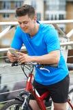 Junger Mann, der Handy während heraus auf Zyklus-Fahrt verwendet lizenzfreie stockfotografie