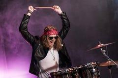Junger Mann, der Hardrockmusik mit den Trommeln eingestellt spielt Stockfotos