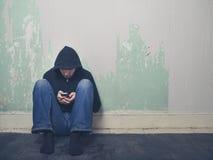 Junger Mann in der Haube unter Verwendung des Smartphone stockbilder