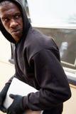 Junger Mann, der in Haus einbricht und Laptop stiehlt Lizenzfreie Stockfotografie