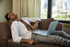 Junger Mann, der Hausarbeit auf Laptop im Schlafzimmer tut lizenzfreie stockfotos