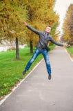 Junger Mann, der in Herbstpark springt Stockfotografie
