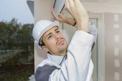 Junger Mann, der herein herauf Fenster für Hurrikan aufnimmt lizenzfreie stockfotos