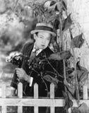 Junger Mann, der hinter einem Baum mit einem Blumenstrauß von Blumen in seinen Händen sich versteckt (alle dargestellten Personen Stockbild