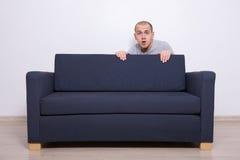 Junger Mann, der hinter einem Sofa sich versteckt Stockfotografie