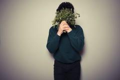 Junger Mann, der hinter Petersilie sich versteckt Lizenzfreie Stockfotos