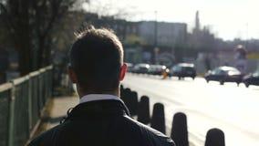 Junger Mann, der hinunter einen Bürgersteig, Zeitlupe geht stock video footage