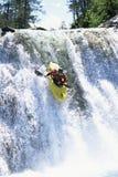 Junger Mann, der hinunter Wasserfall kayaking ist Lizenzfreies Stockfoto