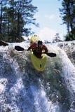 Junger Mann, der hinunter Wasserfall kayaking ist Stockbild