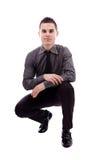 Junger Mann, der in Hockstellung sitzt Lizenzfreies Stockfoto