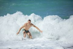 Junger Mann, der hohe Wellen im rauen Meer genießt stockbilder