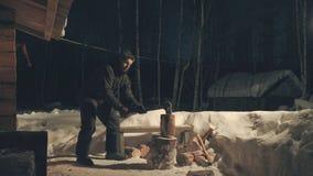 Junger Mann, der Holz im Yard hackt Lizenzfreie Stockfotos