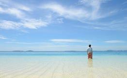 Junger Mann, der Horizont auf tropischem Strand betrachtet Stockfotografie