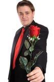 Junger Mann, der Ihnen eine Rose anbietet Stockfotografie