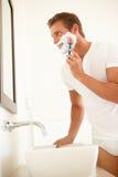Junger Mann, der im Badezimmer-Spiegel sich rasiert Stockfoto