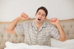 Junger Mann, der im Bett aufwacht und seine Arme ausdehnt stockfotos