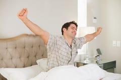 Junger Mann, der im Bett aufwacht und seine Arme ausdehnt lizenzfreies stockbild