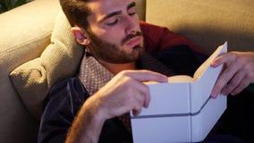 Junger Mann, der im Bett liegt und ein Buch liest stock video