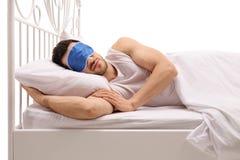 Junger Mann, der im Bett mit einer Augenmaske schläft Lizenzfreies Stockbild