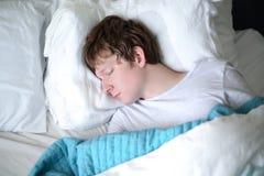 Junger Mann, der im Bett schläft lizenzfreie stockfotos