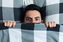 Junger Mann, der im Bett unter der Decke sich versteckt stockbild