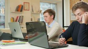 Junger Mann, der im Büro der Laptops auf dem Projekt arbeitet Man ersucht um das Telefon zum Kunden und zu den Aufzeichnungen stock video