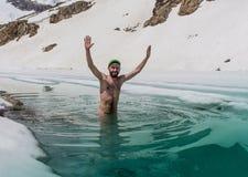 Junger Mann, der im Eisloch badet Lizenzfreies Stockfoto