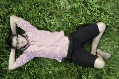 Junger Mann, der im Gras sich entspannt Lizenzfreie Stockfotos