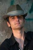 Junger Mann, der im Hut nahe Wand sitzt lizenzfreie stockbilder