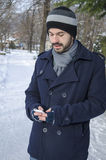 Junger Mann, der im kalten Winter simst Stockfotos