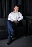 Junger Mann, der im Lehnsessel auf dem dunklen Hintergrund aufwirft Lizenzfreies Stockfoto