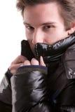Junger Mann, der im Mantel sich versteckt Stockfotografie