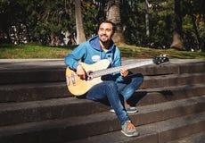 Junger Mann, der im Park in der Lotoslage meditiert Lizenzfreies Stockfoto