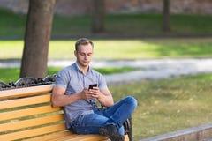 Junger Mann, der im Park mit einem intelligenten Telefon sitzt Stockbilder