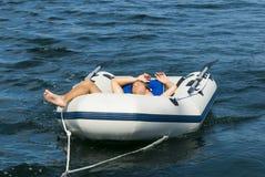 Junger Mann, der im Schlauchboot sich entspannt Stockfoto
