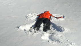 Junger Mann, der im Schnee sich wirft und Schneeengel in der Winterzeit macht stock video footage