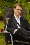 Junger Mann, der im Smoking sich entspannt Stockfotos