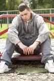 Junger Mann, der im Spielplatz sitzt Stockbilder