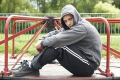Junger Mann, der im Spielplatz sitzt Stockbild